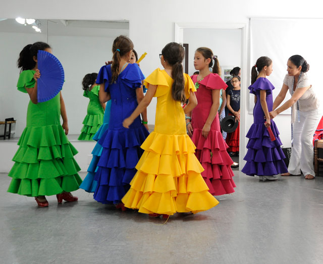 """990f8a57dc66 A GOOD FIT: Seamstress Candi Cruz (far right) checks on the dresses of  young dancers in Linda Vega's dance studio. """"It's a tremendous amount of  work and ..."""